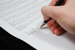 יד מחזיקה עט וחותמת על מסמך