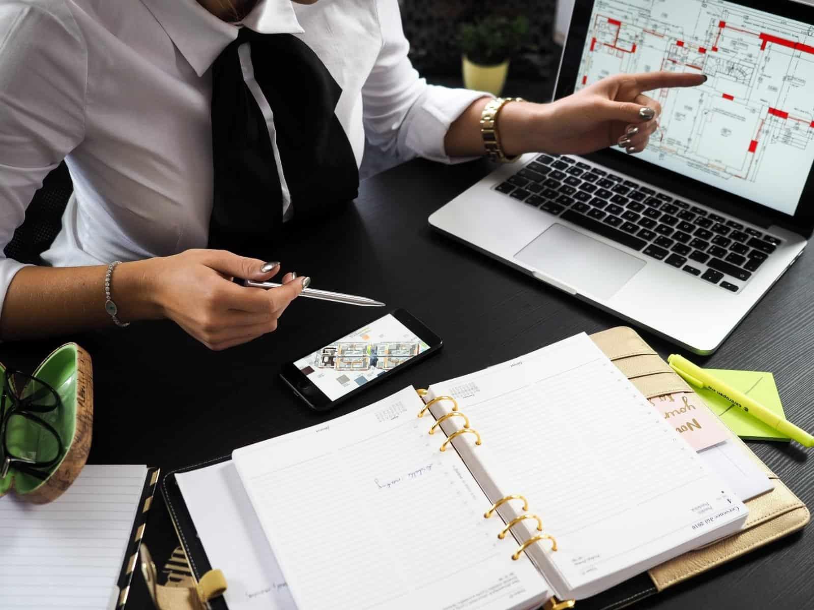 איש במשרד עם מחשב נייד עובר על מסמכים וגרפים
