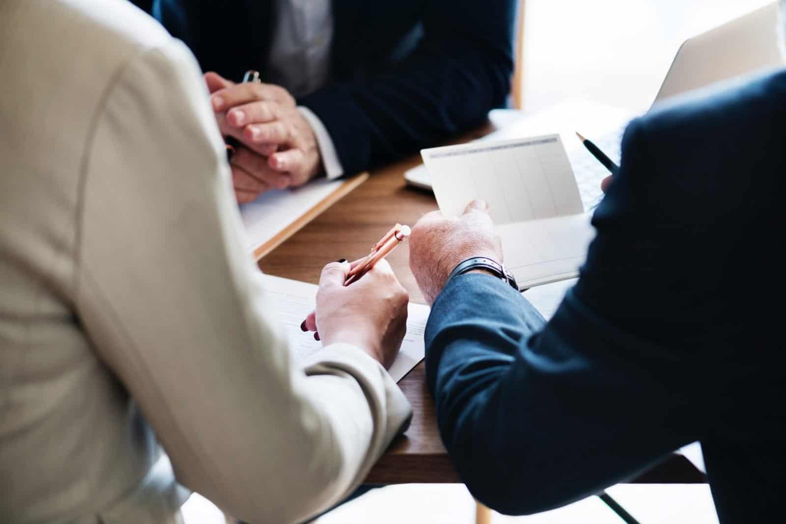 תמונה: אנשים בחליפות יושבים משרד ועוברים על מסמכים